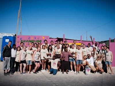 Teen volunteers with their completed painting project at a school overseas