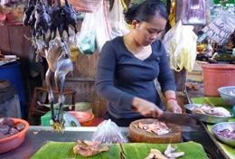 A local entrepreneur in Asia prepares food at her stall funded by the Microfinance Project.