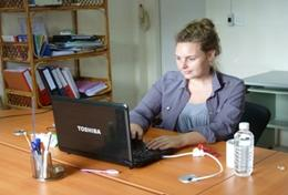 A Microfinance intern works on a business plan for a local entrepreneur in Southeast Asia.