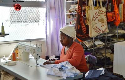 A local woman sews clothing to sell at her small business that International Development interns help her with in South Africa.
