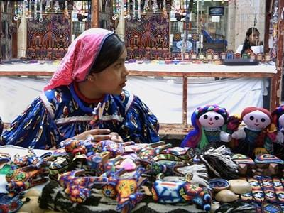 A local woman sells artisan crafts at a market in Mexico.