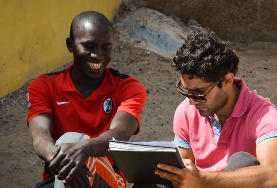 A volunteer intern in Senegal helps a local businessman check his accounts.