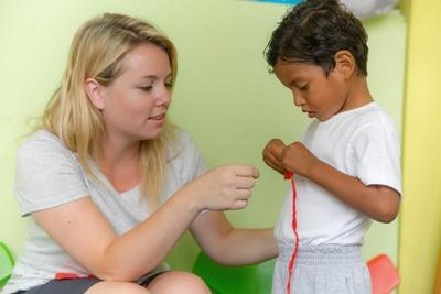 Local child gets help with an activity from a Projects Abroad intern studying social work in Ecuador.