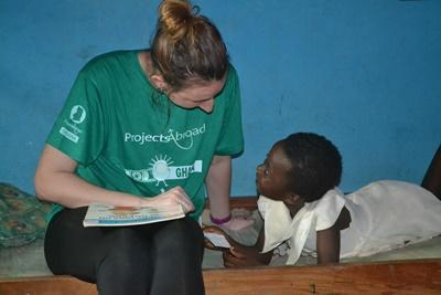 Projects Abroad intern talks with a Ghanaian child in Ghana, Africa at her social work internship placement.