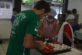 A student on the Social Work Internship serves food during an outreach on his volunteer program.