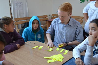 A male volunteer on the Journalism Project leads a workshop activity with children at a school in Romania.