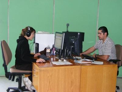 A Journalism intern records a radio broadcast with a local colleague at a station in Mexico.