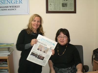Print Journalism intern in Mongolia holds a newspaper she wrote in