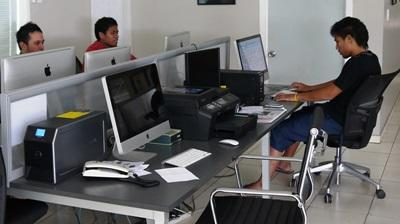 Journalists at a local publication in Samoa work on articles in the office.