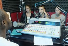 Volunteers on the International Journalism Internship in Jamaica learn from a local DJ at a radio station.