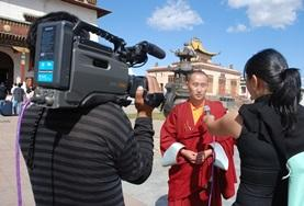 A journalism intern helps conduct an interview with a monk during her volunteer project in Mongolia.