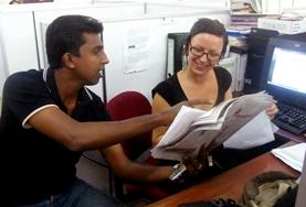 A student volunteer in Sri Lanka on the Journalism Internship discusses her article with a journalist.