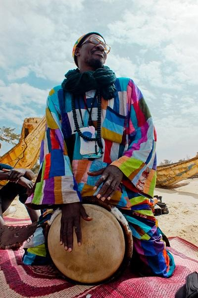 A local man wearing traditional clothing plays an instrument in Senegal, West Africa.
