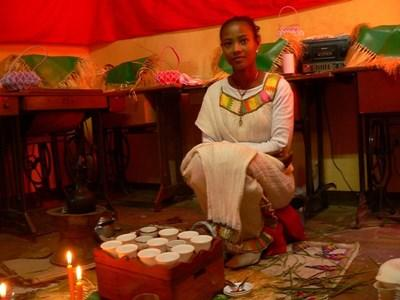 A local girl in traditional clothing conducts a coffee ceremony in Ethiopia.