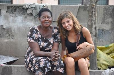 A Projects Abroad volunteer practices her Twi language skills with a local woman in Ghana.