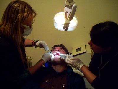 A dentistry student assists a local dentist treating a patient at a clinic in Argentina.