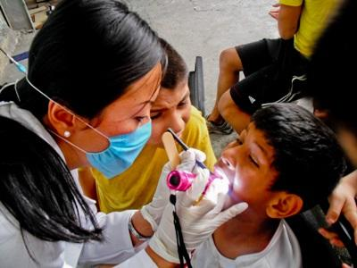 A dentistry student doing her elective in Mexico examines a child's teeth during an outreach.