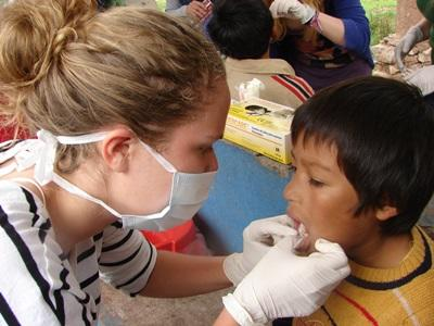 A dentistry student pursuing her elective in Peru examines a child at a medical outreach.