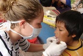 A child's gums are examined by a volunteer on the Peru Dentistry School Elective.