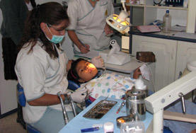 A supervisor in Sri Lanka prepares a child for a dental procedure on the Dentistry School Elective.