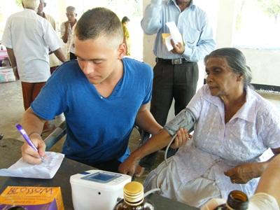 A medical student records a woman's blood pressure readings during an outreach in Sri Lanka.
