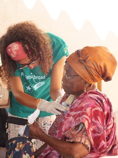 A Togolese woman receives treatment from a Projects Abroad Medical School Elective student.
