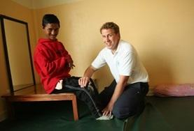 A local man is assisted by a volunteer during her Medical School Elective in Nepal.