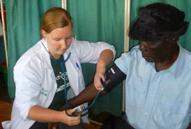 A volunteer on the Tanzania Medical School Elective takes a patient's blood pressure.