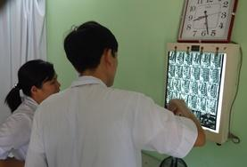 A Medical School Elective volunteer and supervisor talk to a patient in Vietnam.