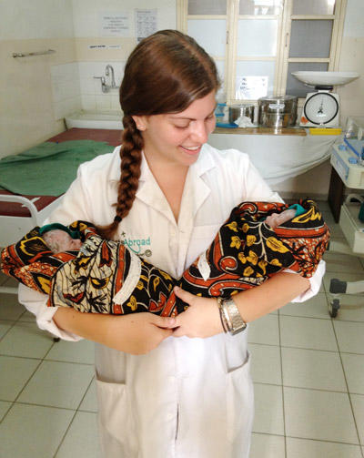 A medical student doing her elective in midwifery holds two new-born babies in Tanzania.