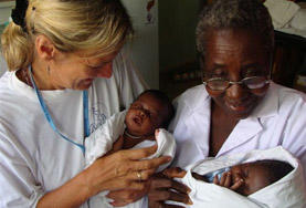 A Midwifery School Elective volunteer and a professional midwife hold a babies in Ghana.