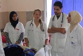 A Midwifery School Elective volunteer listens as her supervisors speak to a patient in Morocco.