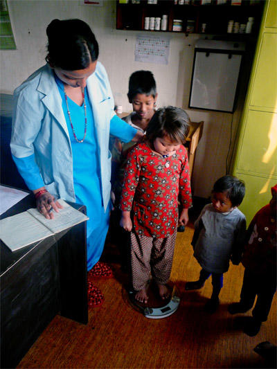 A nursing student doing her elective in Nepal measures weight for a group of children at an outreach.