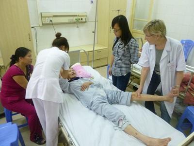 A nurse volunteering in Vietnam helps treat a patient at a hospital in Vietnam.