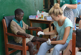 A Nursing School Elective student volunteer in Ghana cleans the wound of a young boy at her placement.
