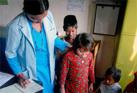 A Nursing School Elective student volunteer helps weigh a child in Nepal as part of her project work.