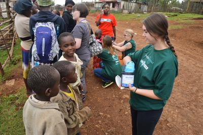 A Pharmacy Elective student distributes  de-worming medication to children in Kenya.