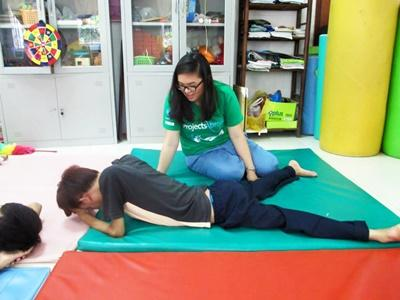 A student doing her Physiotherapy Elective in Vietnam does exercises with a teenager at a rehabilitation centre.