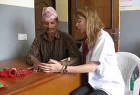 A volunteer on her Physiotherapy Elective in Nepal helps a man move his fingers.