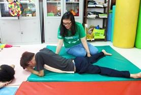 In Vietnam, a student volunteer on the Physiotherapy School Elective helps a man with his stretches on the floor.