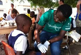 A Nursing School Elective volunteer treats a young boy's wound in a developing country.