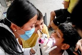 A dentist in Mexico examines a child's teeth while another child observes at a volunteer placement.