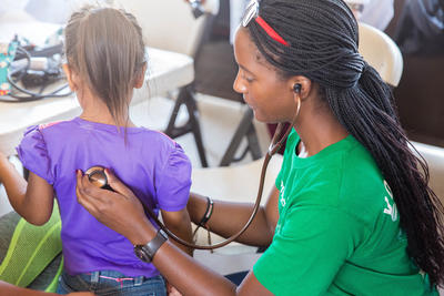 A medical volunteer abroad checks a child's heartbeat at an outreach in Mexico