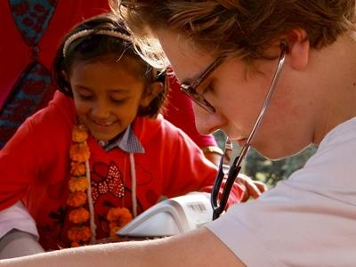 A Projects Abroad Medicine intern helps treat a child during an outreach in Nepal, Asia.