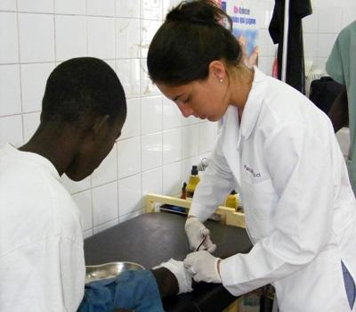 A medical student interning in Senegal helps treat a child under supervision at a hospital.