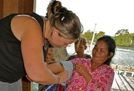 A medical intern in Cambodia checks a woman's vital signs as part of her volunteer project work.