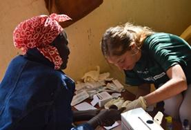 A student volunteer on the medical internship in Kenya checks a woman's vital signs.