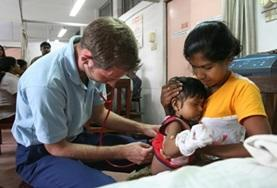 A volunteer medical intern in Sri Lanka checks blood pressure and blood sugar during an outreach project.