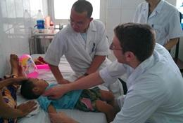 A medical intern and doctor assist a young child in Hanoi, Vietnam.