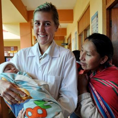 Volunteer with child and its mother at a hospital in Peru on the Midwifery project
